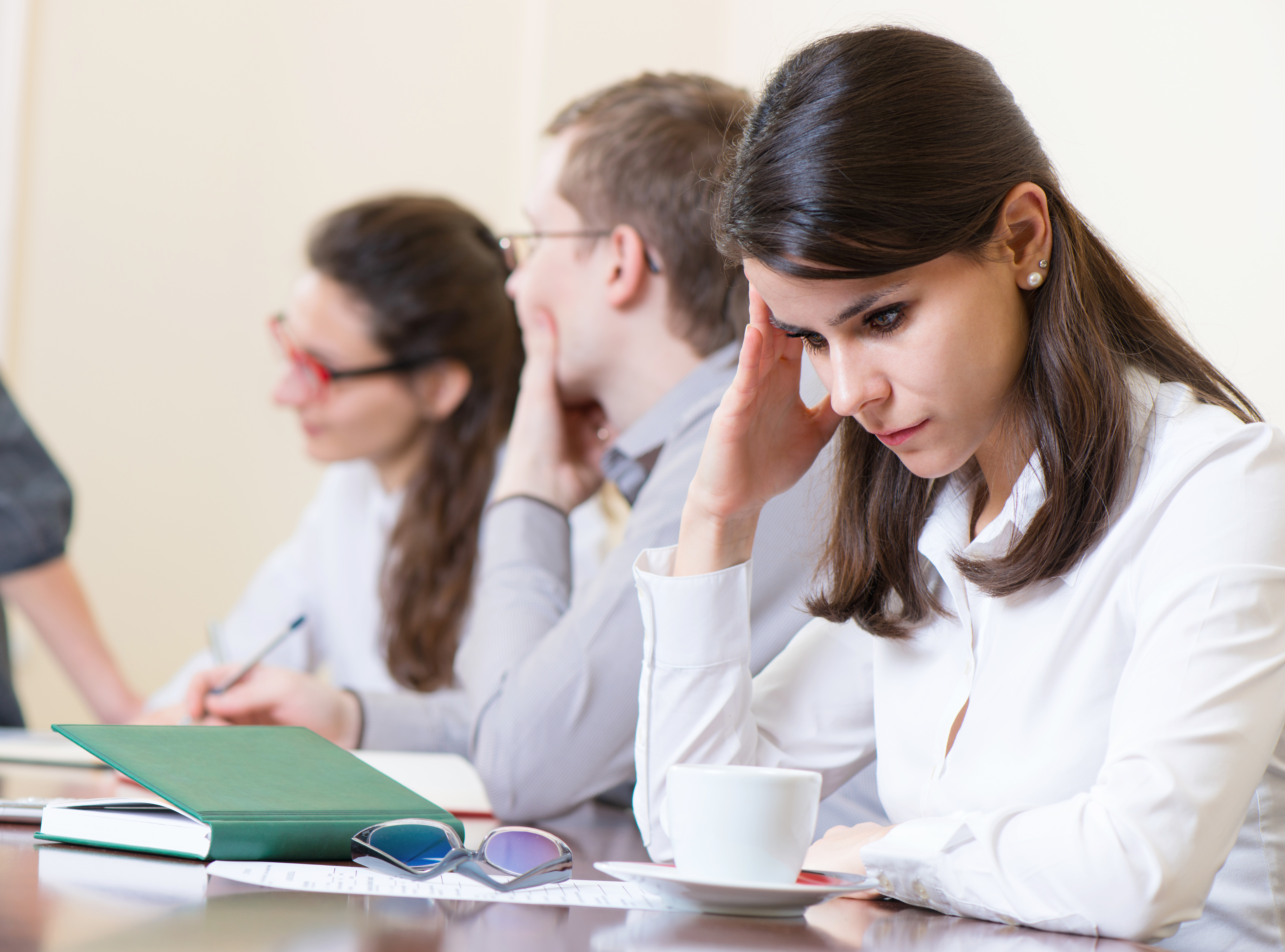 Young tired business woman with headache sitting at seminar