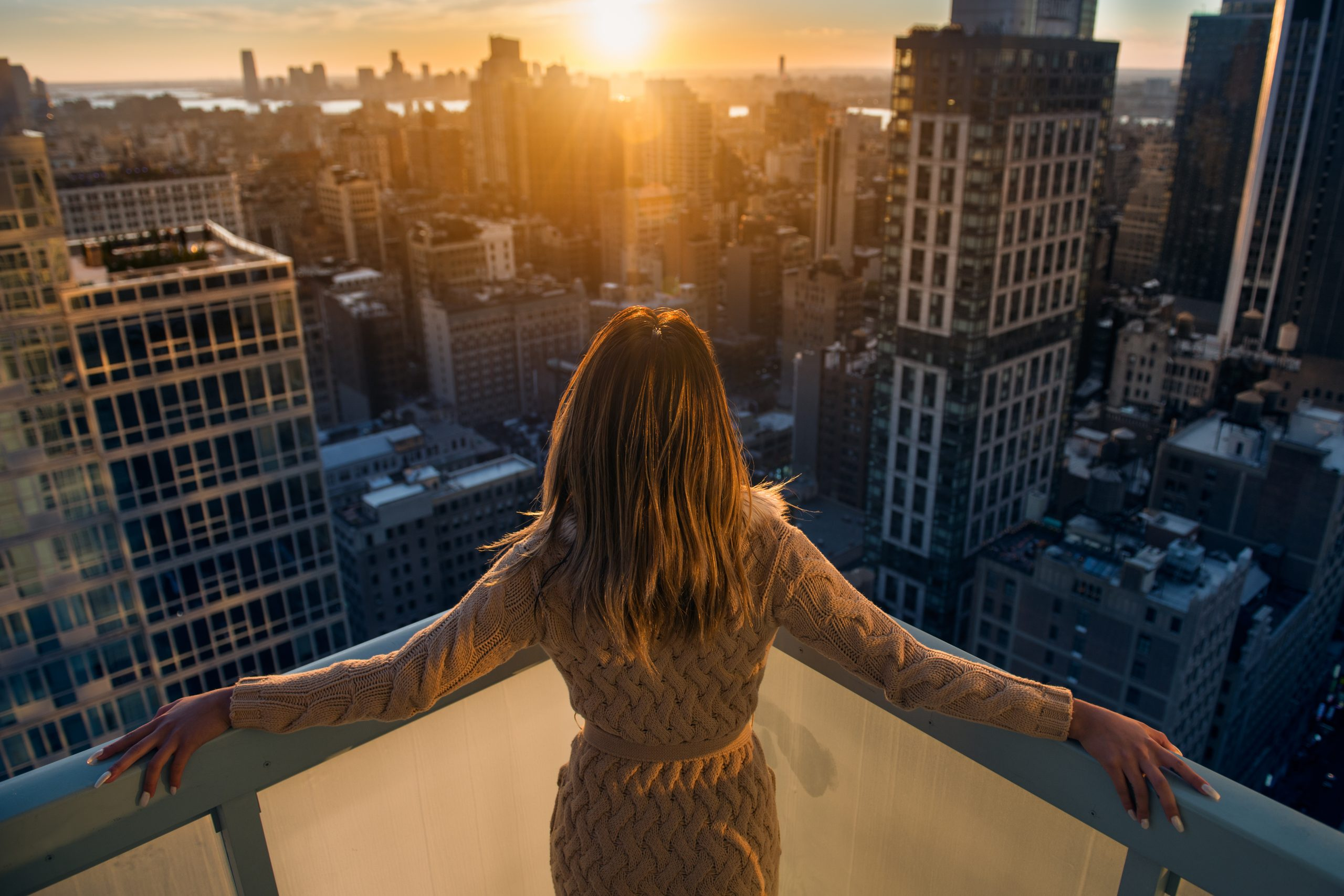 Rich woman enjoy the sunset standing on the balcony at luxury apartments in New York City. Luxury life concept. Succesful B businesswoman relax.