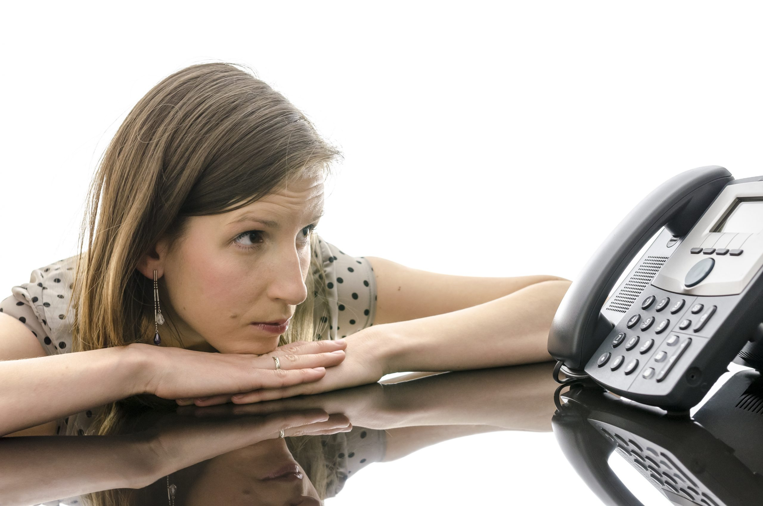 Woman waiting for a phone call while looking at telephone and leaning on a black table with reflection.