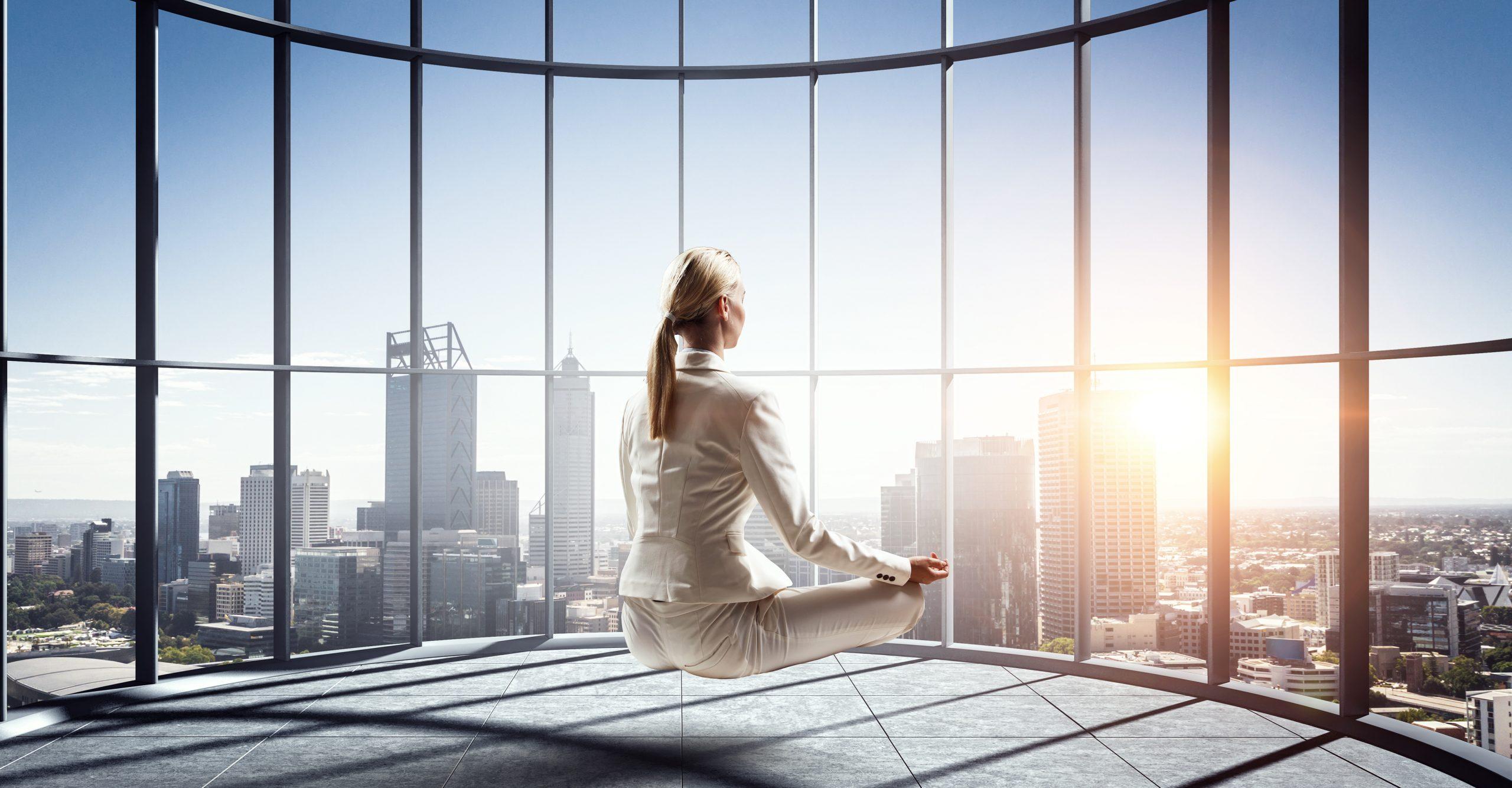 Elegant businesswoman meditating in modern office. Mixed media
