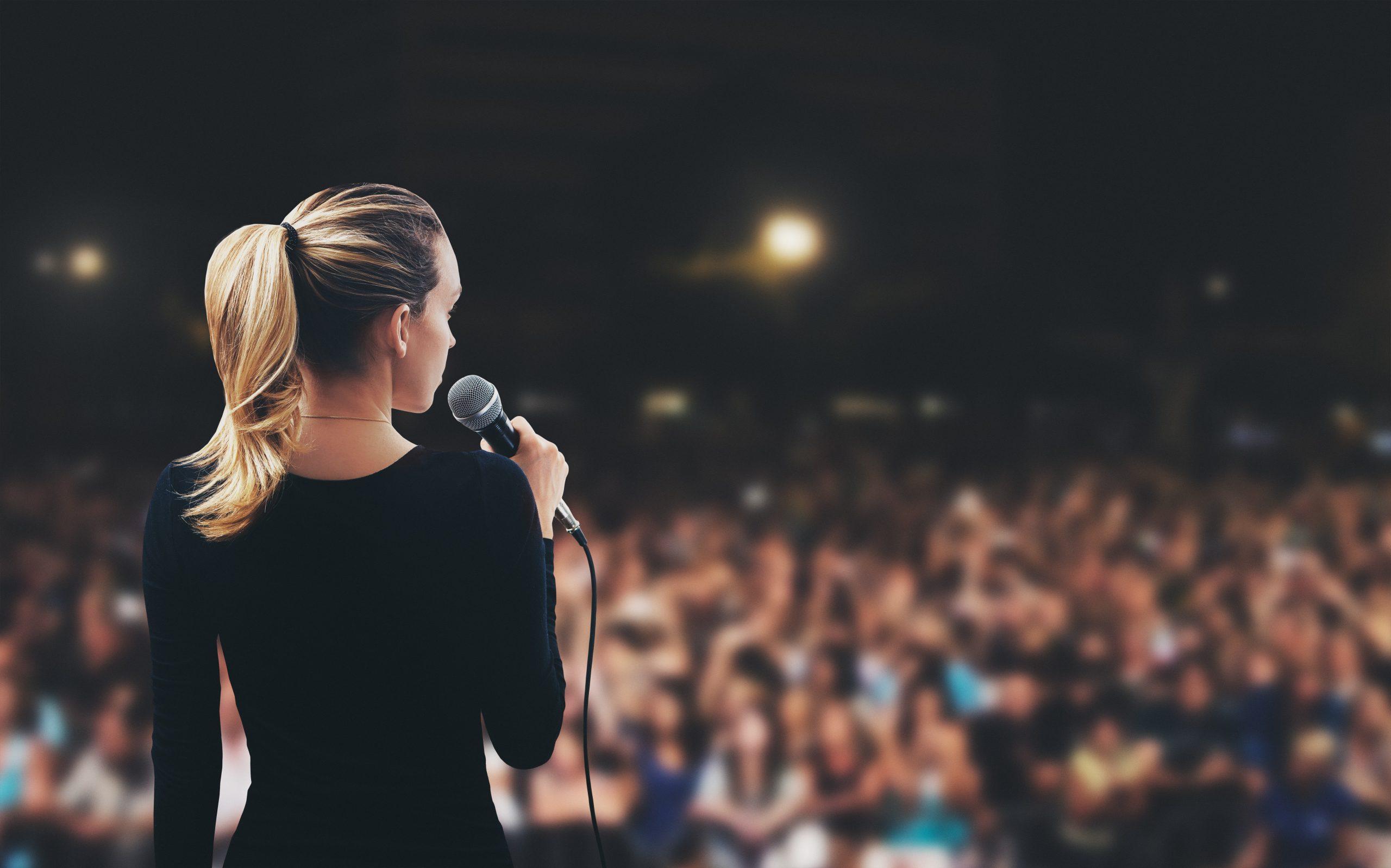 Donna con microfono su palco pubblico